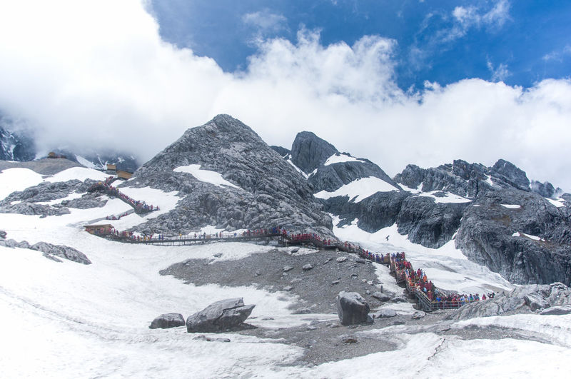 Low Angle View Of Jade Dragon Snow Mountains Against Cloudy Sky On Sunny Day