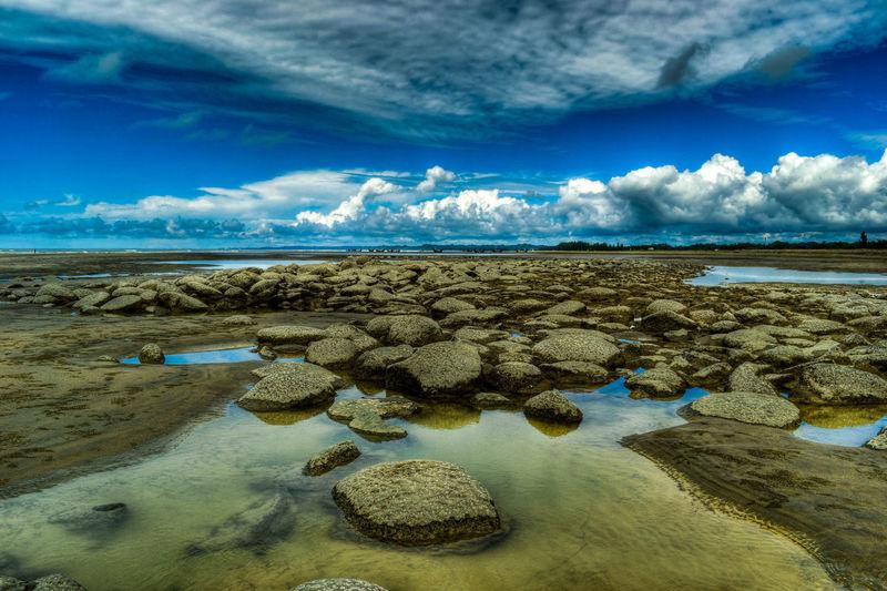 Scenic view of rocky coastline against sky