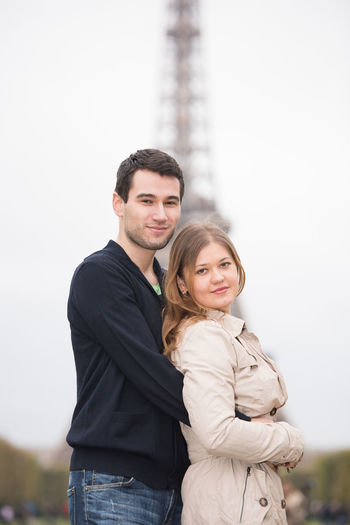 Portrait Of Young Couple Standing Against Sky