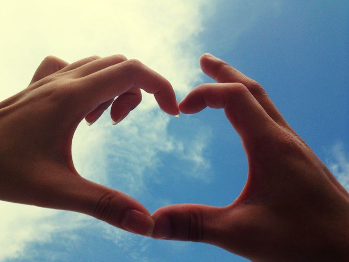 Low angle view of human hands making heart shape against sky