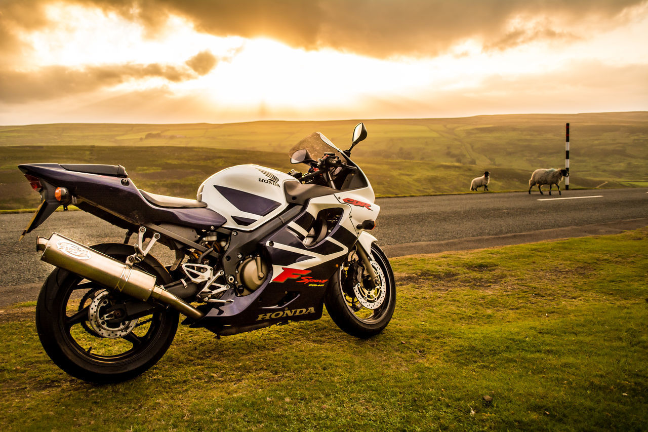 motorcycle, sunset, transportation, cloud - sky, land vehicle, mode of transport, sky, adventure, biker, nature, outdoors, landscape, helmet, real people, motorcycle racing, one person, men, grass, day, mammal, motocross, people