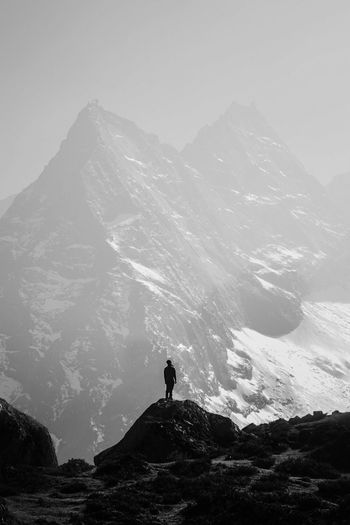 Person standing on rock against mountains
