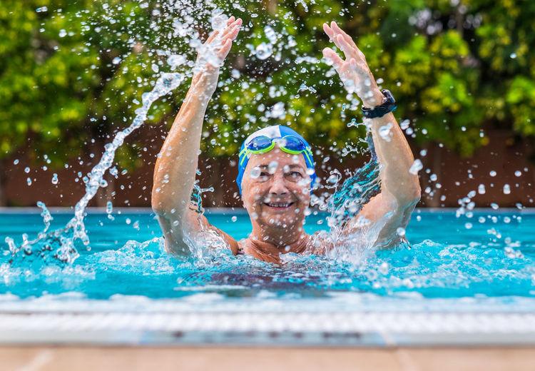 Smiling woman splashing water in swimming pool
