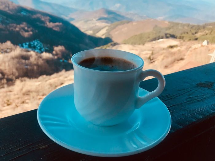 Close-up of coffee cup on table against mountains