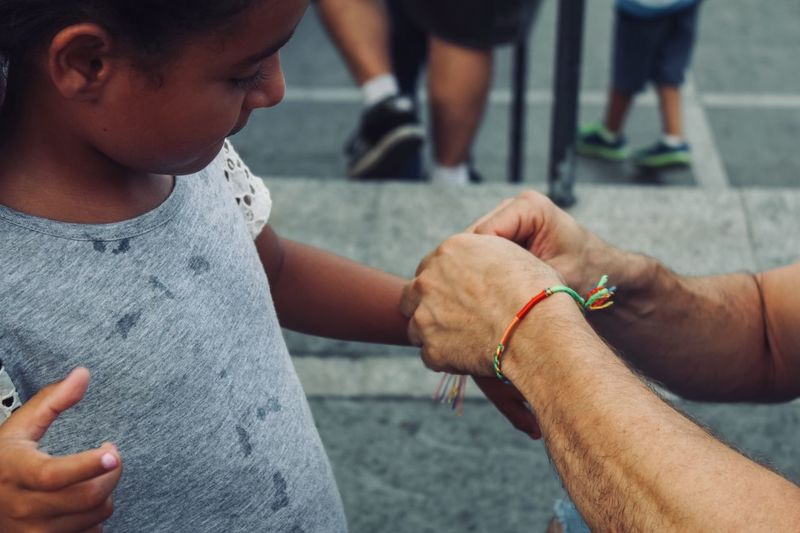 Cropped hands of man tying string on girl arm