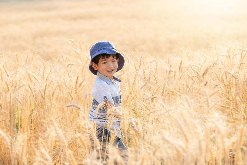 Portrait of smiling boy standing on field