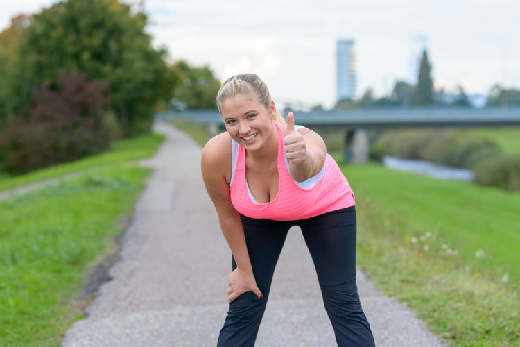 Portrait of smiling young woman exercising on road at park