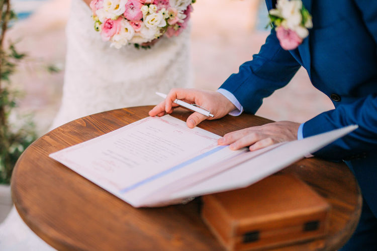 Midsection of man signing agreement during wedding