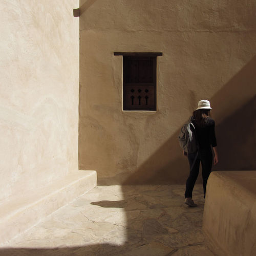 A woman walking in a fort, Nizwa Oman. Ancient Architecture Backpack Building Exterior Built Structure Day Fort Historical Building History Leisure Activity Lifestyles Nizwa Nizwa Fort Oman One Person Outdoors People Rear View Standing Traveller Walking Window