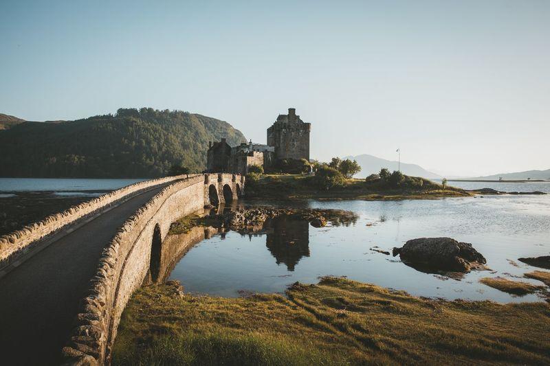 Bridge leading towards castle in sea against clear sky