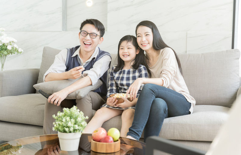 happy asian family watching tv together on sofa in living room. family and home concept Asian  Family Happiness Happy Happy People Family Time Home House Daughter Parent Father Mother Dad Mom Love Lifestyles Living Room ASIA Japanese  Korean Thai Taiwan MOVIE Watching Popcorn Television Sofa Togetherness Group Of People Sitting Women Smiling Furniture Casual Clothing Females Adult Front View Young Adult Leisure Activity Bonding Smile Fun Portrait Girls