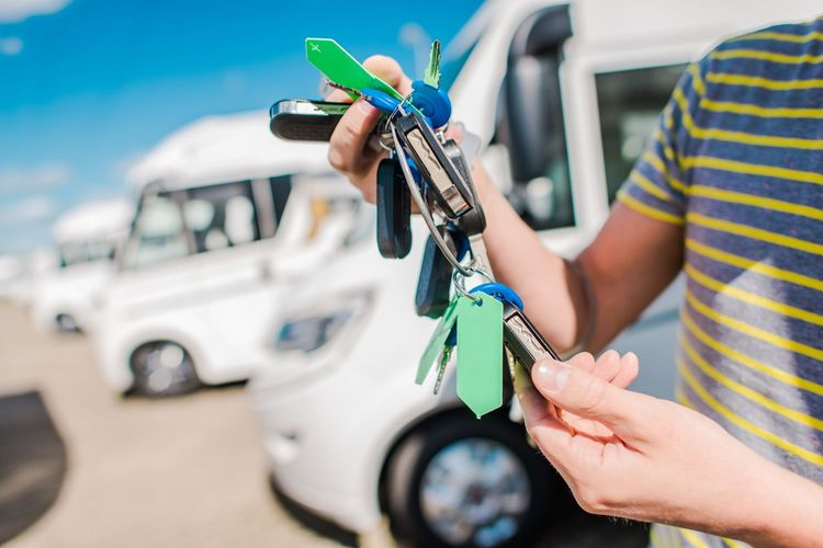 Midsection of man holding keys in parking lot