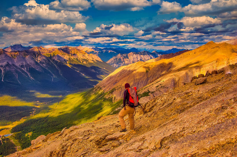 Rear view of person on mountain against sky