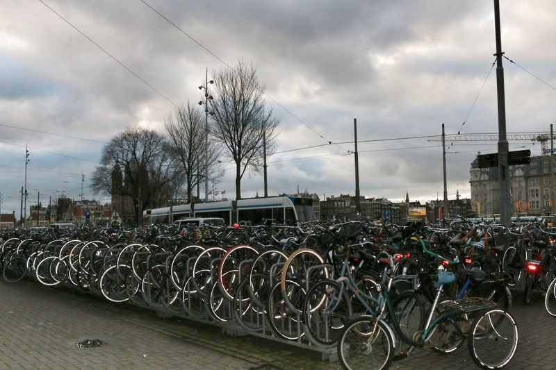 Bicycles Parked In Row Against Cloudy Sky