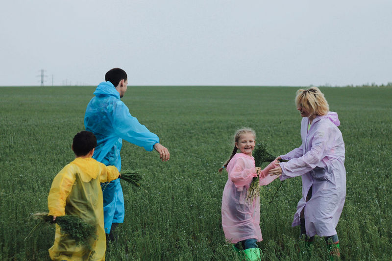 Happy family playing on field against sky