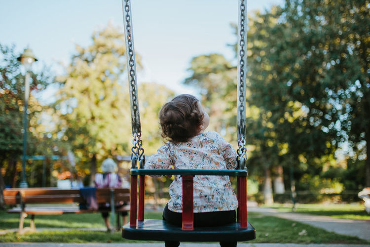 Rear view of baby girl sitting on swing at park