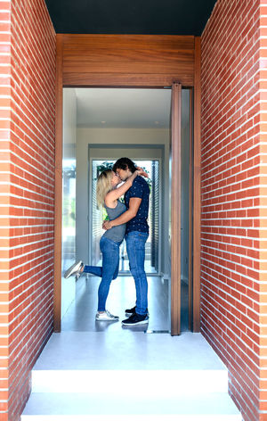 Couple kissing at the entrance of their new house Cardboard Box Collaboration Couple Entrance Happiness Home Household Man Moving Relationship Woman Young Boxes Caucasian Door Estate Female House Male Move New Home Partner Two People Vertical Weight