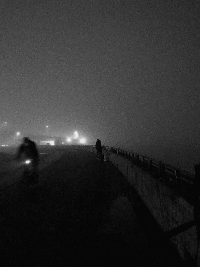 PEOPLE WALKING ON ILLUMINATED BRIDGE AT NIGHT