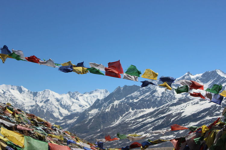 Low angle view of colorful prayer flags at himalayas against clear blue sky