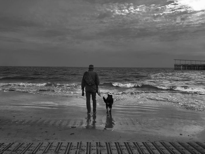 A day at the beach. Coney Island NYC Photography Brooklyn Cold Day At The Beach Cold Day Friendship Bw_collection Blackandwhite Beach Photography Before The Storm Love Pet Gray Day Grey Gray Black And White FiveSigmaPhoto Sea Water Beach Real People Sky Land Horizon Over Water Horizon Togetherness Day Outdoors