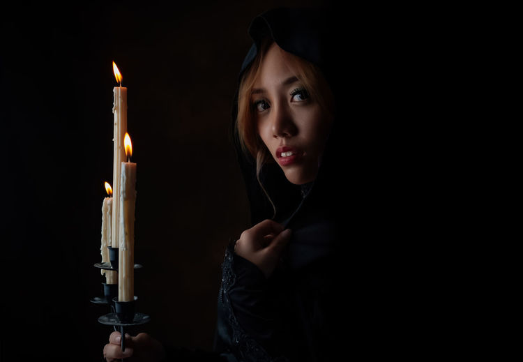 Close-Up Portrait Of Young Woman By Lit Candles Against Black Background