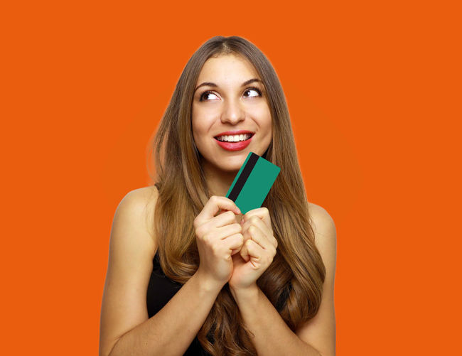 Happy young woman holding credit card while looking away against orange background