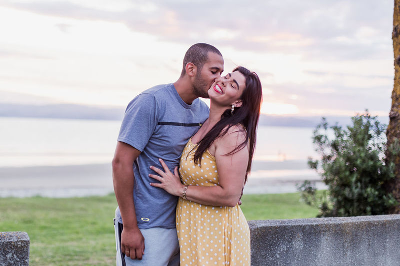 Man Kissing Woman While Standing Against Sky During Sunset