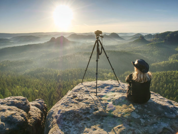 Woman photographer with leather hat conquer highest peak. mountain landscape. . hipster hiker style.
