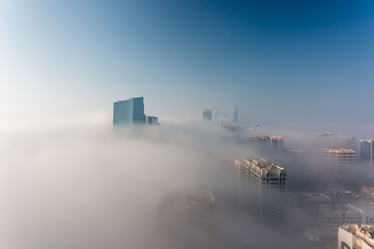 Modern buildings in abu dhabi against fog