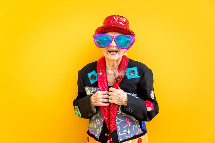 Portrait of smiling senior woman against yellow background