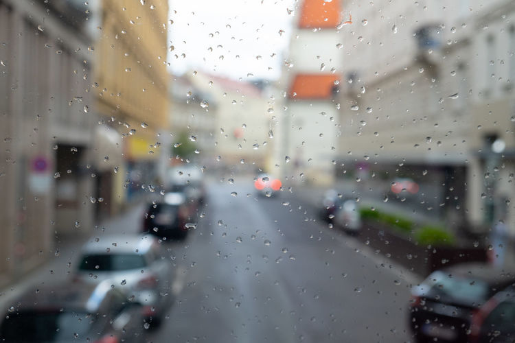 Wet Drop Glass - Material Rain Window Water Transparent Rainy Season RainDrop Mode Of Transportation Transportation City Focus On Foreground Windshield Selective Focus Blurred Background Cityview City Life Defocused Street Road