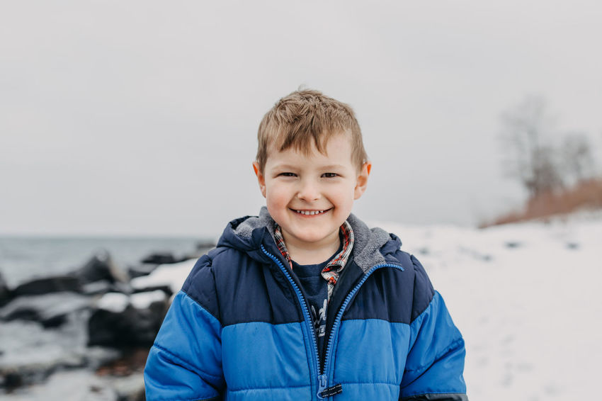 Spring Fling Eye Contact Kindergarten Lake Superior North Shore Minnesota Rocky Beach Winter Adventure Blue Coat Boy Cold Temperature Collecting Rocks Day Lake Nature One Person Outdoors Overcast Day Playful