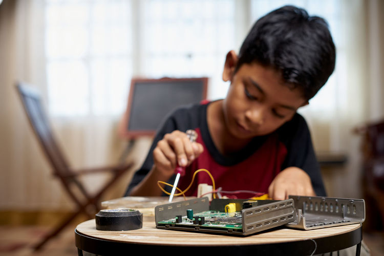 Side view of boy using laptop on table
