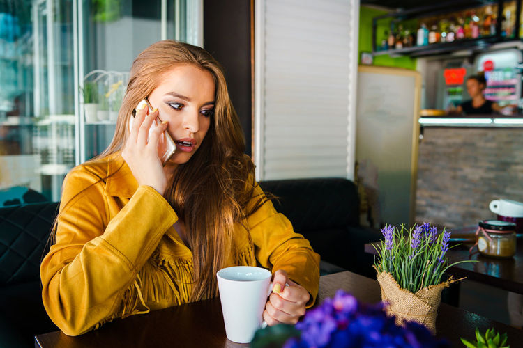 Shocked young woman using mobile phone while sitting in cafe