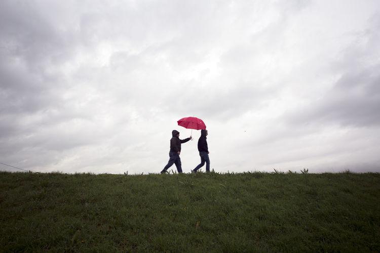 Two men walking on grassy field against cloudy sky