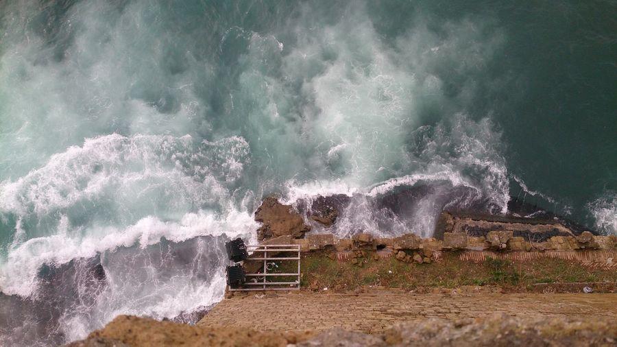 Waves splashing on rocks by sea