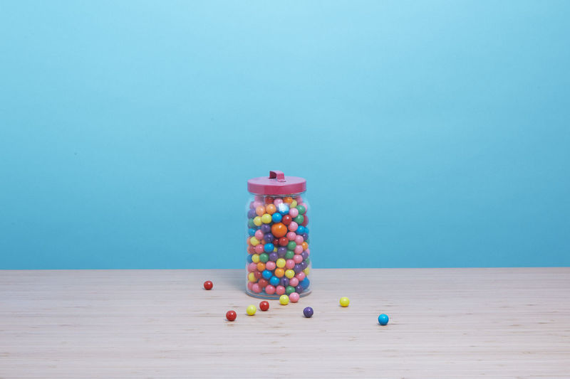 Gumball machine and gum balls spilling on a table.