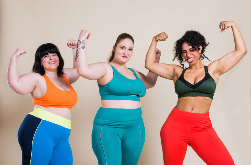 Happy friends flexing muscles standing against colored background
