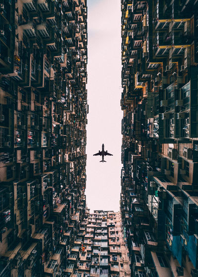 Right in the middle of Hong Kong's most dense buildings. Hong Kong Airplane Architecture Building Exterior Built Structure City Cityscape Day Flying Low Angle View No People Outdoors Sky Skyscraper Symmetry Transportation