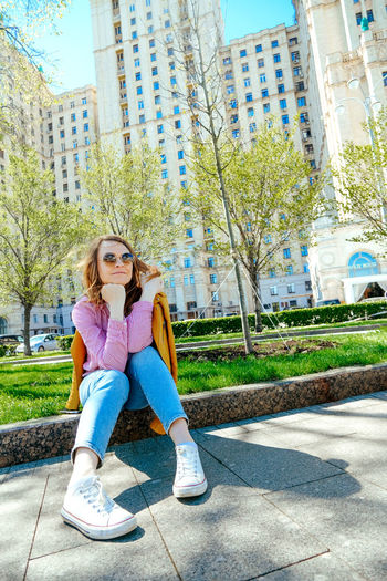 Full length portrait of woman sitting in city