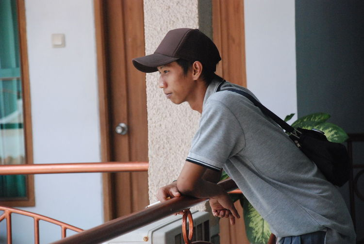 Side view of young man looking away while standing on railing