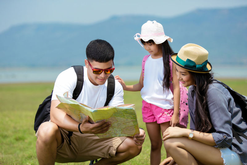 Bonding Book Casual Clothing Child Childhood Females Front View Hat Holding Leisure Activity Lifestyles Nature Outdoors People Publication Real People Sitting Three Quarter Length Togetherness Women