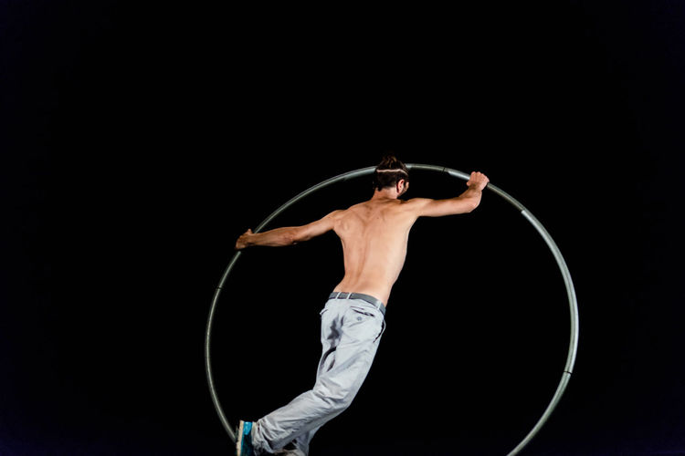 Circus Acrobat Adult Balance Black Background Circle Copy Space Expertise Full Length Holding Indoors  Men Motion One Person Performance Plastic Hoop Skill  Sport Studio Shot Vitality Young Adult