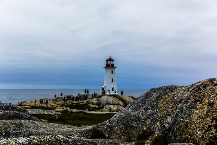 Architecture Beach Beauty In Nature Building Exterior Built Structure Day Finding New Frontiers Grass Horizon Over Water Large Group Of People Lighthouse Nature Outdoors Peggy's Cove People Protection Rock - Object Sea Sky Travel Destinations Water