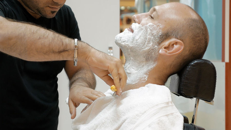 Midsection Of Barber Doing Shaving Of Mature Man In Salon