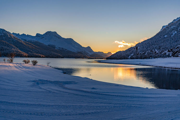 View of beautiful sunet at lake silvaplana, switzerland, in cold winter evening with foreground snow