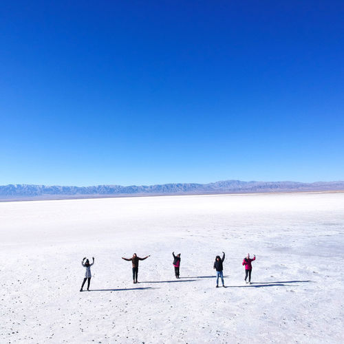 Group of people on landscape against clear blue sky