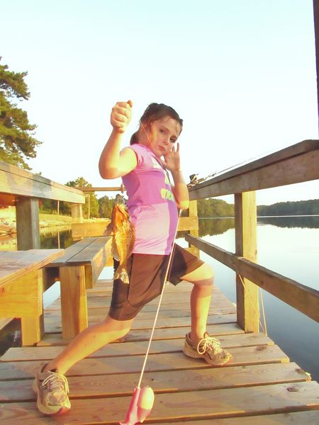 Catch And Release Girl Fishing Anglers Fishing Relaxation People Fishing Pier Fishing Dock Proud Moment  Showing Expression Emotion Proud Moment  Showing Off Vacation Young Adult Childhood Leisure Activity Children Only Child One Girl Only One Person Girls Outdoors Standing Full Length