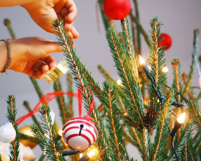 Cropped hands decorating christmas tree