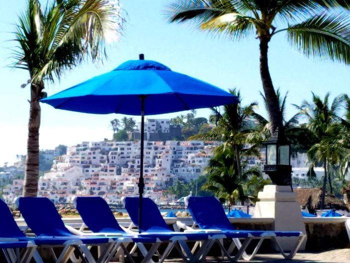 Lounge chairs by swimming pool against blue sky